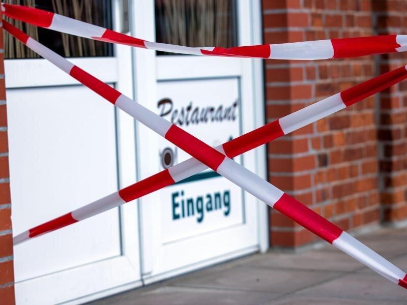 Mit rot-weißem Absperrband ist der Zugang zu einem Restaurant in Boizenburg abgesperrt. Außenbereiche von Lokalen sollen dem Entwurf zufolge erst öffnen, wenn die Inzidenz 14 Tage stabil unter 35 bleibt.