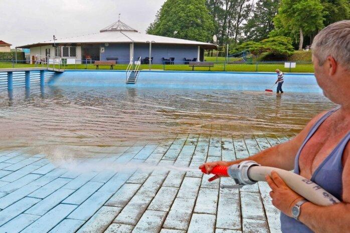 Schwimmmeister Gerd Hochmuth muss das Becken im Crossener Bad ablassen und reinigen, nachdem die Sturzflut aus dem Birkengrundbach und von einem benachbarten Feld am Samstag Schlamm hineingespült hatte. Nach nicht einmal einem Tag Öffnung ist das Bad nun wieder geschlossen.
