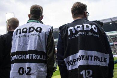 Alltag im Profi-Fußball: Dopingkontrolleure warten nach dem Abpfiff am Spielfeldrand auf die zur Kontrolle ausgelosten Spieler.