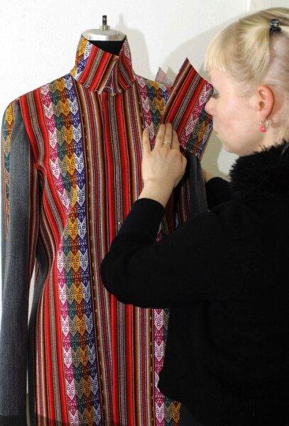"""<p class=""""artikelinhalt"""">Sylvia Schmidt arbeitet an einem Mantel. Darunter soll das Model ein T-Shirt tragen, auf dem ein gestickter Vogel an die Nazca-Linien erinnert.</p>"""