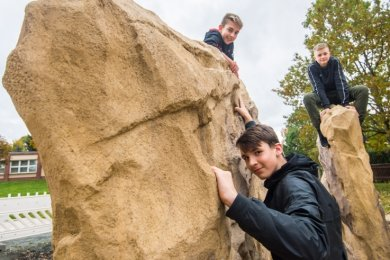 Tim Gerschler, Jason Beckert und Anthony Anders (von links) von der Oberschule Neukirchen probieren die neue Klettergelegenheit auf dem Spielplatz an der Jahnstraße in Neukirchen aus.