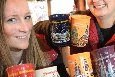 Viele Tassen und noch mehr verschiedene Glühweine. Zur Auswahl, die Marie Blechschmidt und Jacqueline Stein (v. l.) vergangenes Jahr auf dem Chemnitzer Weihnachtsmarkt zeigten, kommt jetzt noch eine dazu.