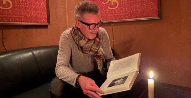 Nico Kunz blättert in einem gefundenen Porträt-Buch.