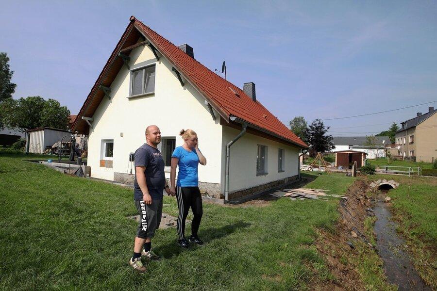 Jasmin Maibach und Benjamin Gottschling stehen vor ihrem Haus, das sie aufgrund der Schäden im Erdgeschoss verlassen mussten.