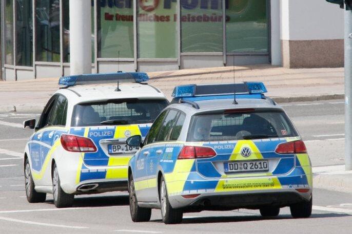 Ein Mann wird in Handschellen abgeführt und in einem Streifenwagen aufs Polizeirevier gebracht.