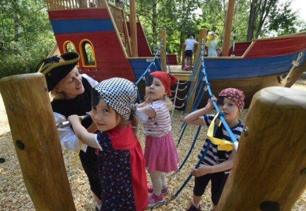 Erzieherin Kerstin Eberhardt durfte mit den Kindern Eleanor, Anna und Emma (von links) mit als Erste auf das neue Piratenschiff im Garten der Kita an der Fritz-Fritzsche-Straße. Die Mädchen hatten sich passend dazu als Piratinnen verkleidet.