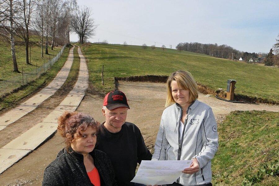 Ramona Köpsell (links) sowie Heike und Detlef Parthum schauen sich den Lageplan des Gebietes an. Die Wiese im Hintergrund soll Bauland werden.