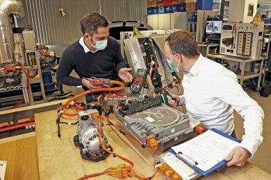 Elektromobilität beschäftigt auch das VW-Bildungsinstitut: Im Bild sind Tobias Müller, Leiter der Weiterbildung Technik (links), und Ricardo Schönherr, Leiter Produktionssysteme bei VW Sachsen, zu sehen.