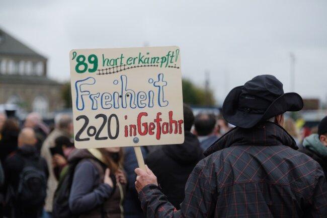 """Ein Teilnehmer einer Demonstration der Bewegung """"Querdenken 351"""" trägt ein Schild auf dem Theaterplatz. Viele Menschen protestierten gegen die Coronapolitik der Bunderegierung."""