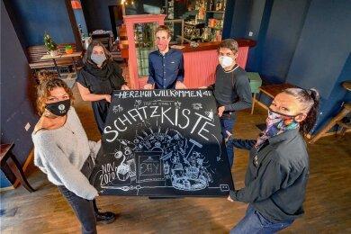 """Das war die """"Schatzkiste"""": Josephine Berger, Fatima Medjaji, Maximilan Berndt, Mathias Weiß und Luisa Milner (von links) vom Team des Cafés """"EmmasOnkel"""" mit dem Schild, das auf den alternativen, zeitlich begrenzten Laden hinwies."""