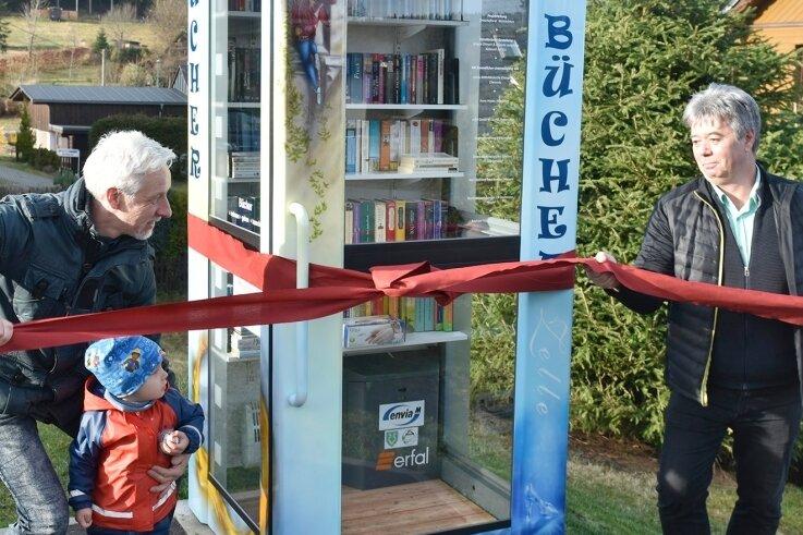 So ein Geschenk packt man gerne aus: Ortschaftsratsmitglied Jörg Hoyer (links) und Airbrush-Künstler Jürgen Zinnert aus Aue, der die Bücherzelle gestaltet hat, weihten sie feierlich ein.