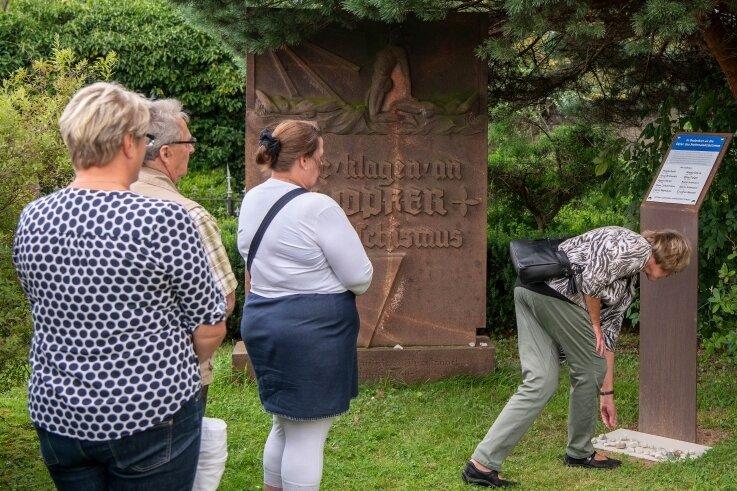 Besucher der Einweihung legen gemäß jüdischer Tradition Steine am Fuß der Gedenkstätte ab.