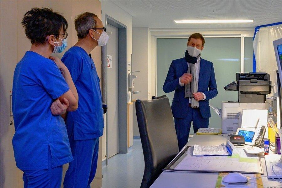 Bei einem Besuch von Sachsens Ministerpräsident Michael Kretschmer (rechts im Bild) erörterten Klinikmitarbeiter am Freitag die angespannte Lage durch die Covid-19-Pandemie.