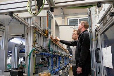Trotz beengter Verhältnisse läuft die Arbeit reibungslos: Hier sind die LSA-Mitarbeiter Hendrik Neubert (vorn) und Clemens Hilbert bei der Inbetriebnahme einer Fertigungsanlage zu sehen.