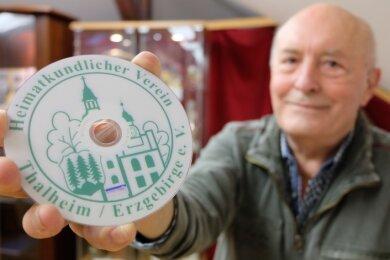 Vereinsmitglied Dieter Auerbach mit einer DVD des Heimatkundlichen Vereins. Darauf ist das Symbol mit den drei Tannen zu sehen.