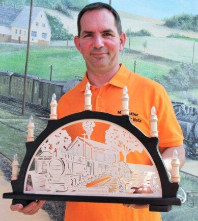 Vereinsvorsitzender Markus Nestler mit dem Schwibbogen, der auf der Facebookseite der Stadt Thum ersteigert werden kann.