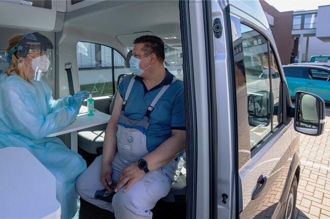 VW-Mitarbeiter Udo Strewe wird im neuen Impfmobil auf dem Betriebsgelände von Volkswagen Sachsen in Zwickau von Werksärztin Nicole Walther gegen das Coronavirus geimpft.