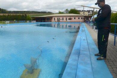 Jörg Dölling steuert den Unterwasserbodensauger, mit dem das 50-Meter-Schwimmbecken des Freibades Reumten-grün gereinigt wird.