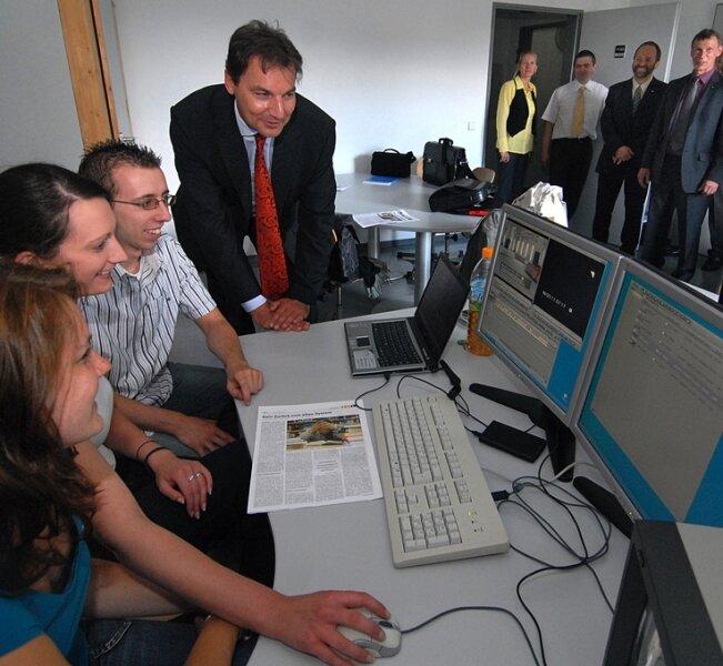 Ricarda Hans, Mandy Schulze und Felix Schulze (v. l.), Multimedia-Studenten der Hochschule Mittweida, zeigen dem Envia-Tel-Geschäftsführer Thomas Wellhausen, wie sie einen Videofilm schneiden.