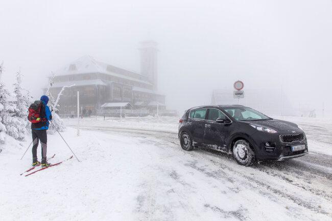 Ein Skiwanderer im Schnee vor dem Fichtelberghaus.