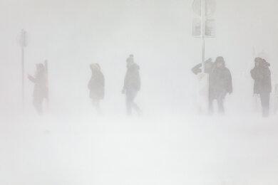 Spaziergänger im Schneetreiben auf dem Fichtelberg.