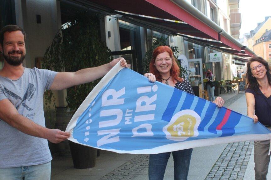 Frank Müller, Katrin Hoffmann und Kirsti Brandt-Wiedbusch (von links) schwenken die Fahne für die Bewerbung um die Kulturhauptstadt.