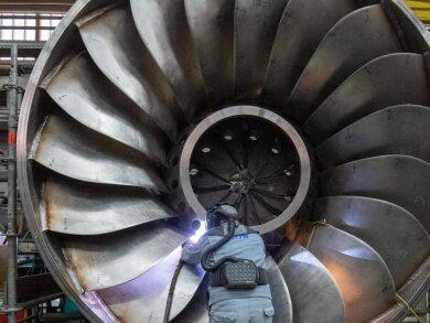 Ein Angestellter in einer Maschinenbaufirma arbeitet an einer Wasserturbine.