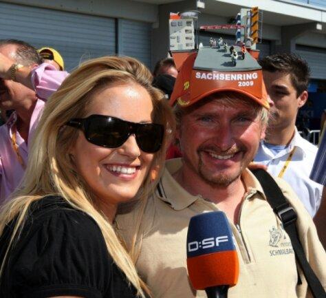 """<p class=""""artikelinhalt"""">Am Ring suchen die Fernsehleute nach Geschichten für ihre Sender. DSF-Moderatorin Andrea Kaiser fand am Freitag Udo Naumann, der jedes Jahr eine besondere Kopfbedeckung für den Sachsenring bastelt.</p>"""