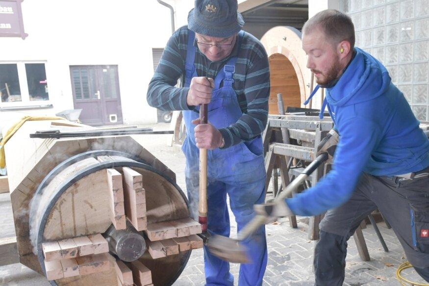 Für das Hammerwerk in Bergisch Gladbach: Hans Karel (links) und Nico Wagener, Mitarbeiter im Mühlenbaubetrieb Schumann, ziehen die Ringe auf die Wasserradwelle aus Eiche auf und verkeilen diese danach fest mit Buchenkeilen.