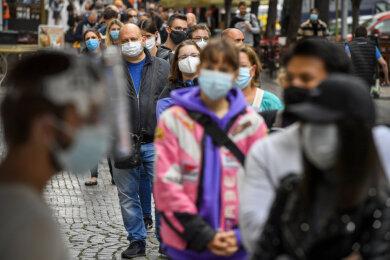 Menschen mit Mundschutz stehen an der Sammelstelle am Wenzelsplatz Schlange, um sich auf Covid-19 testen zu lassen. In Tschechien breitet sich das Coronavirus weiter rasant aus. Die Bundesregierung sprach am Mittwochabend eine Reisewarnung für die am stärksten betroffene Hauptstadt Prag aus und erklärte sie zum Risikogebiet.