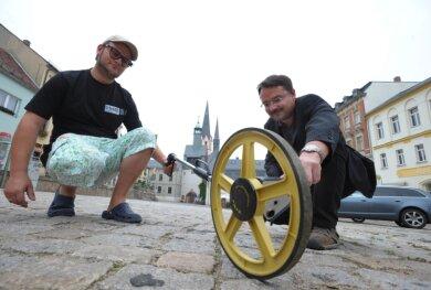 """<p class=""""artikelinhalt"""">Enrico Oswald (r.) und Felix Georgi haben sich mit den Gegebenheiten des Burgstädter Marktplatzes vertraut gemacht. Für die Lichtshow zum Stadtfest wurde der Platz am Montag vermessen.</p>"""
