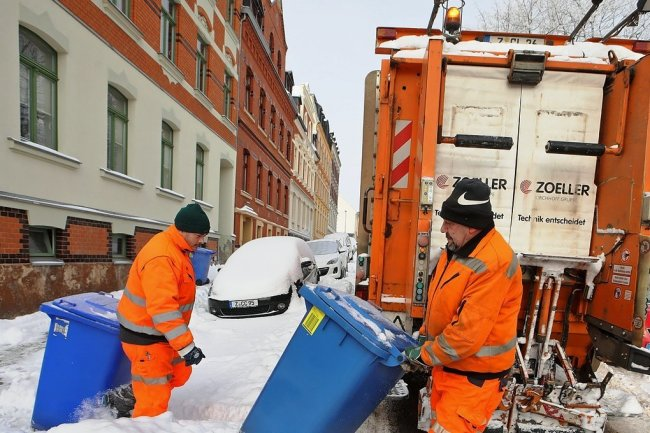 Roman Friedrich (rechts) und sein Kollege Norman Schmidt bei der Entsorgung der blauen Tonnen an der Weberstraße in Meerane.