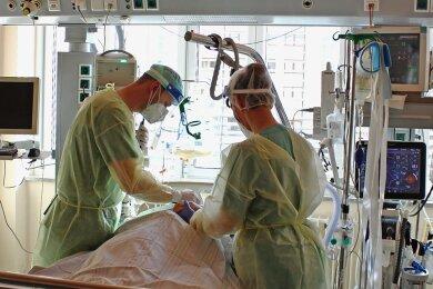 Ein Arzt (links) und eine Pflegerin bei der Behandlung eines Patienten auf der Covid-Intensivstation im Heinrich-Braun-Klinkum Zwickau.