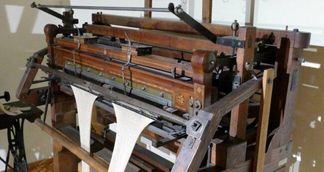 Aus dem Jahr 1860 stammt dieser Handkulierstuhl, bei dem alle Fäden noch per Hand gelegt wurden. Maschinelle Hilfe wurde erst später möglich.