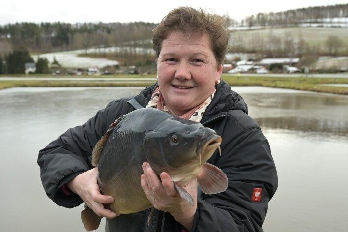 Corina Rockstroh, die die Fischzucht Schröder in der vierten Generation leitet, präsentiert ein Prachtexemplar von einem Karpfen. Diese Fische sind vor dem Jahreswechsel unangefochtene Favoriten im Verkauf.