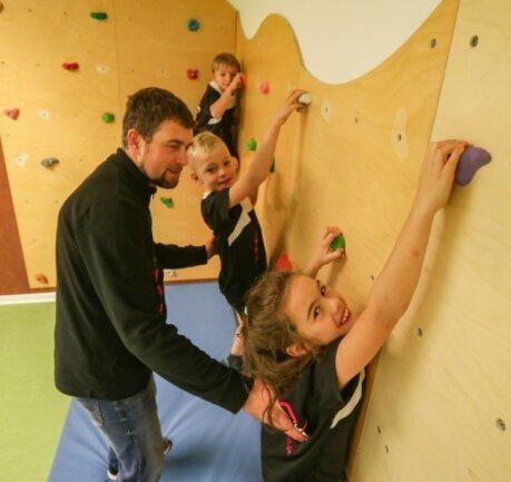 Auch eine Kletterwand gibt es in den neuen Räumlichkeiten des Sporthortes. Oskar, Nicolas und Lea (von links) haben diese unter der Aufsicht von Erzieher Falk Dressel bereits getestet.