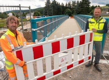 Polier Erik Steinert (l.) und Bauleiter Ronny Oehme beseitigten die Absperrungen und gaben damit die Brücke frei.