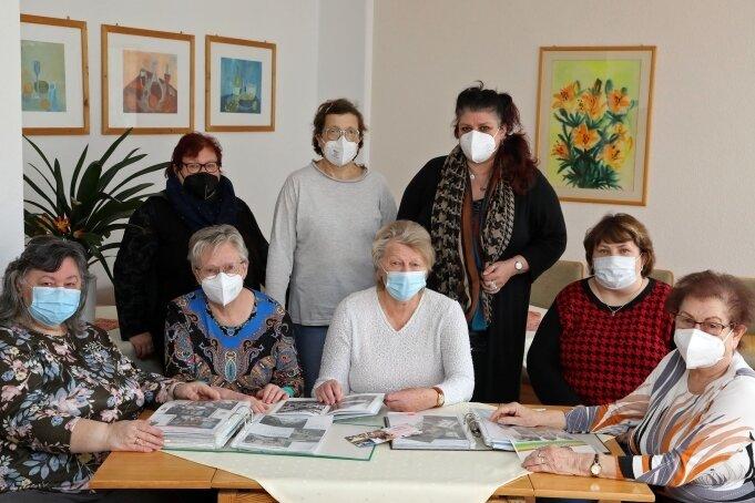 Das Team des Frauenzentrums beim Blättern in alten Fotos.