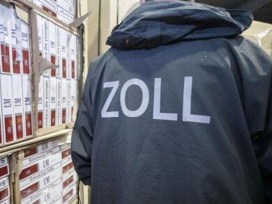 Ein Zollbeamter steht in einer Verwahrstelle des Zolls vor konfiszierten Paletten mit geschmuggelten Zigaretten.
