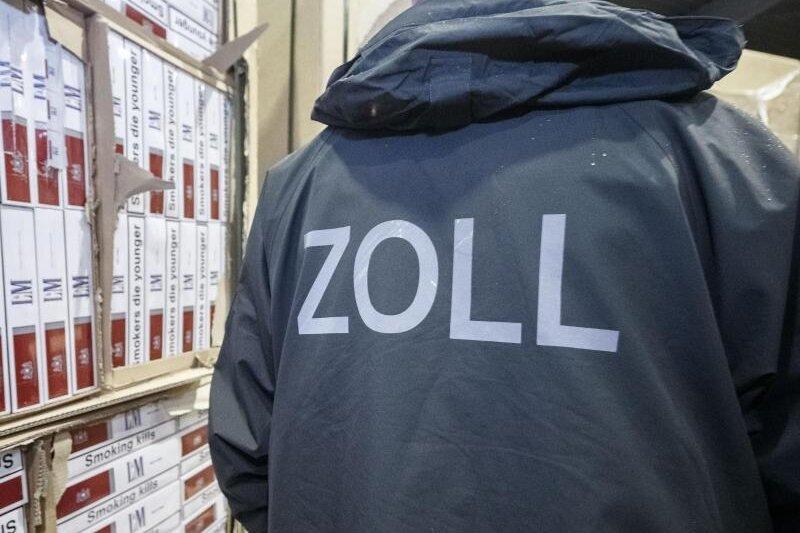 Ein Zollbeamter steht in einer Verwahrstelle des Zolls vor konfiszierten Paletten mit geschmuggelten Zigaretten (Symbolbild).