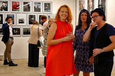 Beatrice Kober (links) und Michaela Oheim plaudern zur Ausstellungseröffnung mit Fotograf Chris Gonz über seine Promi-Portraits.