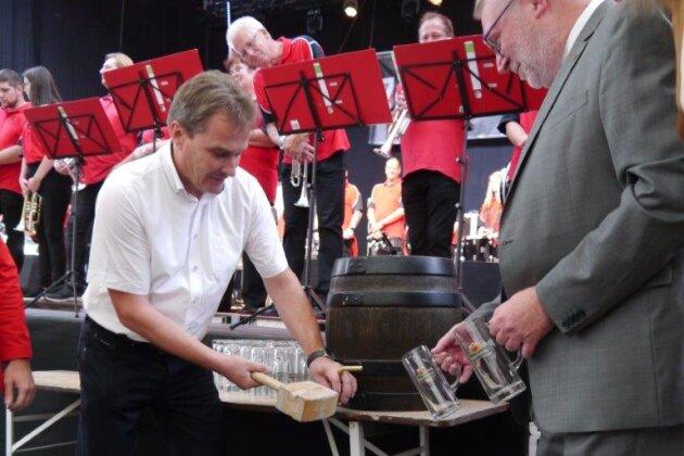 Mittweidas OB Ralf Schreiber (links) benötigte zwar mehrere Schläge, aber dann floss das Freibier zum Auftakt des Altstadtfestes am Freitagabend. Diesmal wurde er beim Ausschank unterstützt von Mittelsachsens Landrat Matthias Damm.