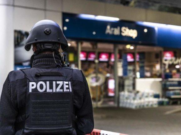 Ein Polizist steht vor der Tankstelle in Idar-Oberstein, an der ein Angestellter von einem Mann erschossen worden ist.
