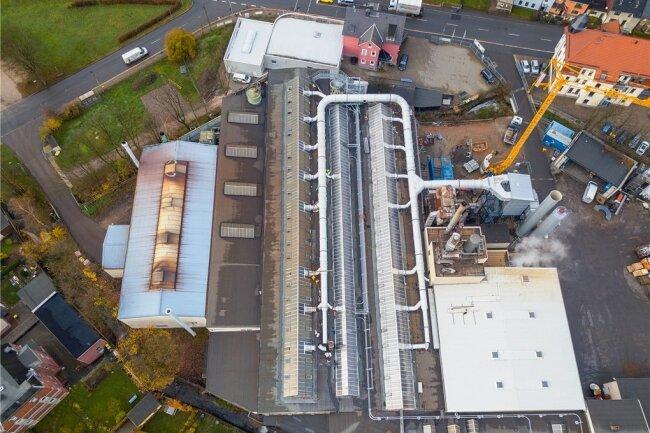 Die Abgasreinigung: Über Rohre wird die Luft unterm Hallendach abgesaugt und zum Filterturm (rechts) geleitet.