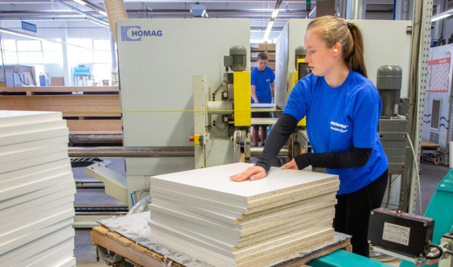 Esther Kaden (vorn) und Armin Witte gehören zu den drei jungen Leuten, die zurzeit in der Ratiomat Einbauküchen GmbH Leubsdorf einen Ferienjob ausüben. Die Bearbeitung von Bauteilen an einer Kantenbearbeitungsmaschine gehört zu den Tätigkeiten für die Schüler.