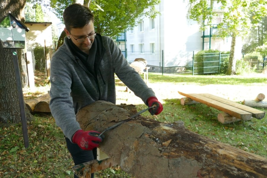 Marcus Gillner entrindet eine Baumstammhälfte. Daraus fertigen AGH-Teilnehmer Bänke, die an Wanderwegen um Zschopau aufgestellt werden.