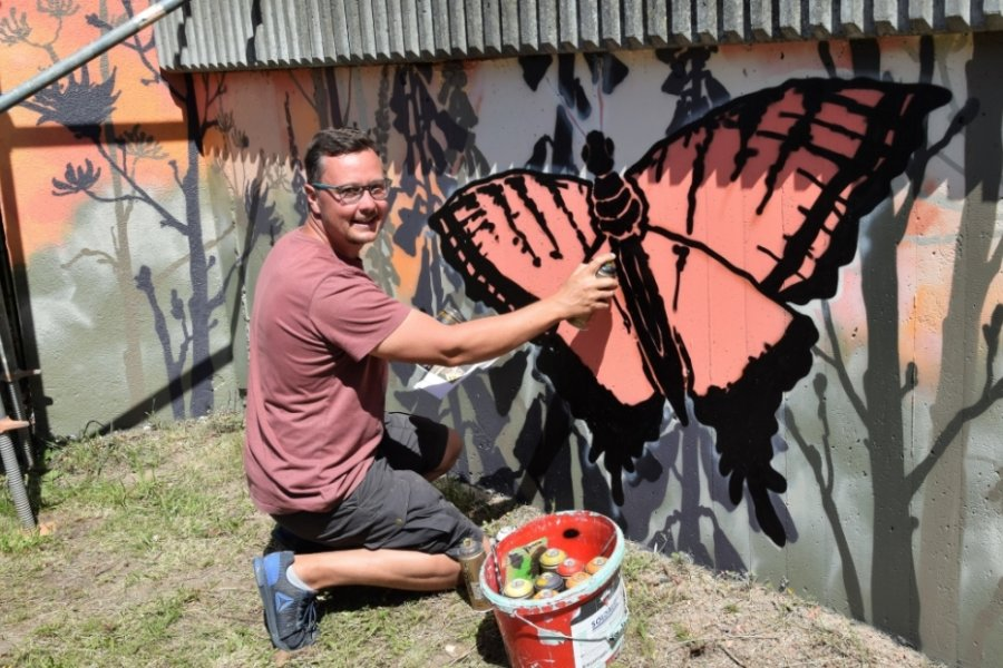 André Wolf aus Kürbitz hat die Stützmauer zum Bahndamm hin im Freizeitgelände am Kreisverkehr in Lengenfeld mit Schmetterlingen und Blumen besprüht.