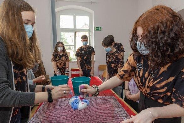 """Elisa Fränzl (l.) und Elisa Seliger von der Schülerfirma """"sob-shop"""" stellen ein T-Shirt in Batik-Technik her. Doch Corona erschwert den Verkauf."""