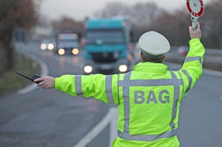 Ein Beamter des Bundesamtes für Güterverkehr winkt am B-93-Rastplatz Crossen einen Laster für eine Routinekontrolle heraus.