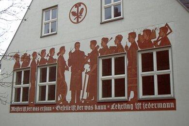 """Der Wandfries am Beruflichen Schulzentrum Reichenbach stellt verschiedene Gewerke dar. Darunter steht: """"Meister ist, der was ersann. Geselle ist, der was kann. Lehrling ist jedermann."""""""